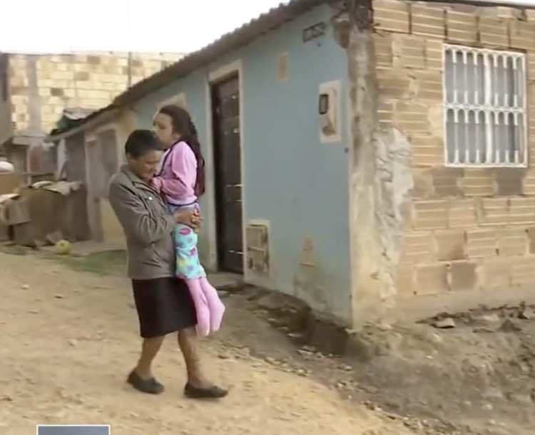 La nonna porta in braccio la nipote alla fermata dello scuolabus