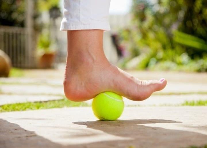 Massaggio ai piedi con una palla da tennis